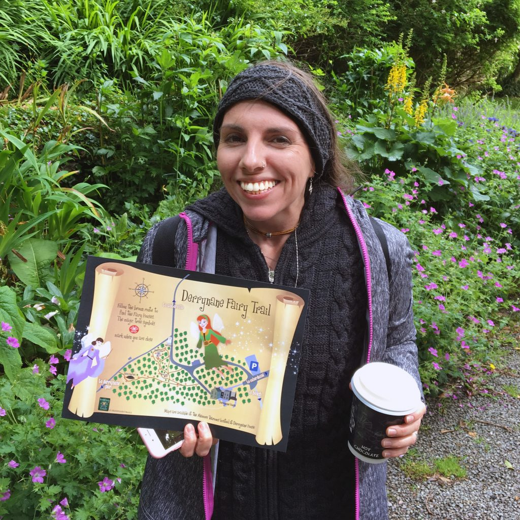 Blythe holding a fairy trail map and a cup of coffee in Derrynane, Ireland
