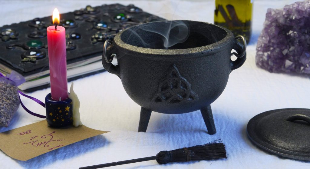Cast-iron cauldron with triqueta design, candle, sigil, book of shadows, and besom.