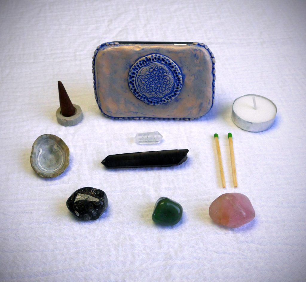 Altoids tin travel altar decorated with polymer clay, with crystals, incense, tea light candles, an offering shell, and matches