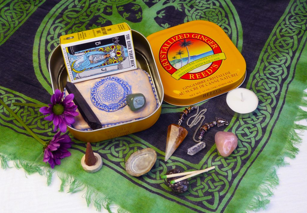 Ginger candy tin travel altar with altar cloth, tarot cards, travel deity tin, crystal wand, pendulum, matches, incense, and tea light candles.