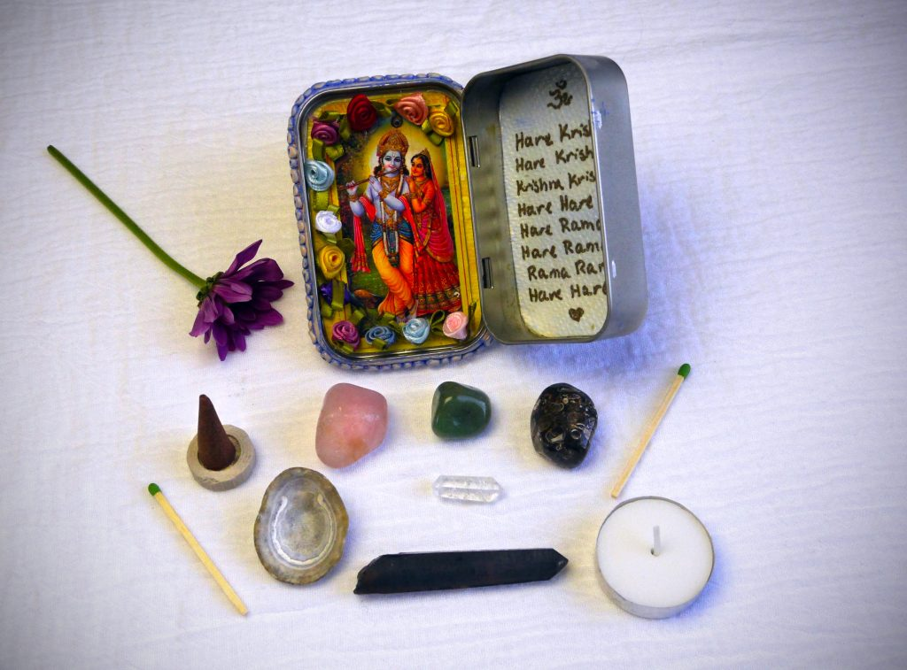 Travel altar with Sri Sri Radha Krishna, mantra, crystals, incense, a tea light candle, and a tiny wand.