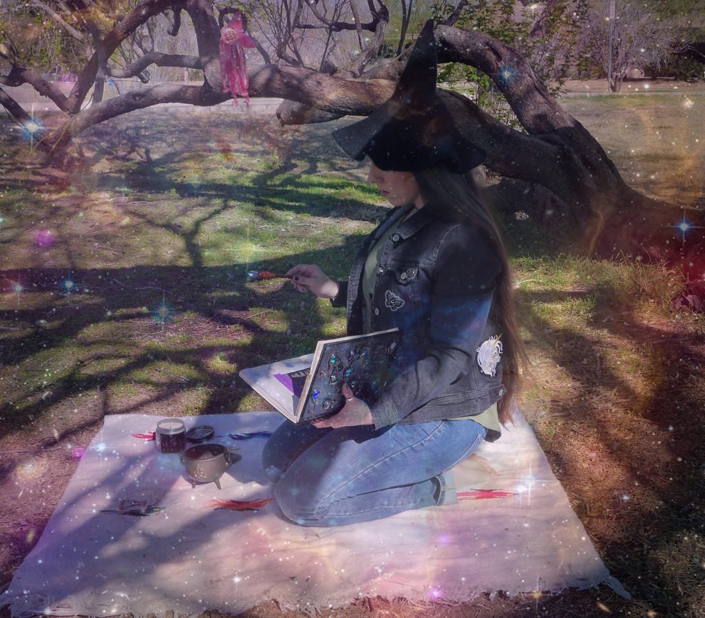 Witch wearing witch hat holding spell book and magick wand with magical sparkles.