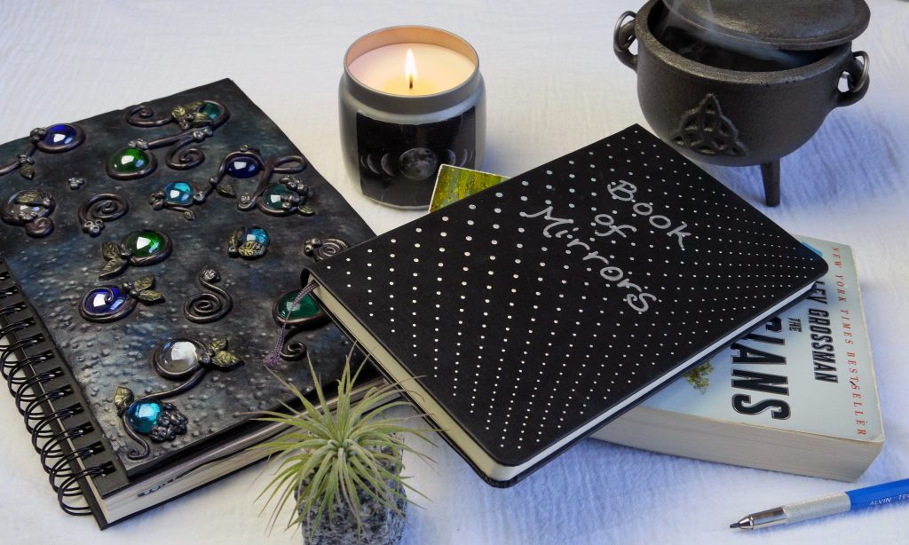 Book of Shadows, Book of Mirrors, magical journals, cauldron, candle.