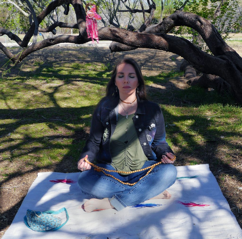 Woman meditating outside sitting under a tree, chanting on mala beads.