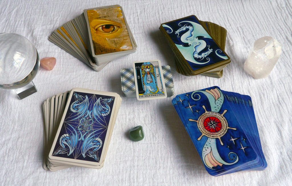 In the center: mini Rider-Waite-Smith, top left: Haindl Tarot, top right: Fantastical Tarot, bottom left: Dragon Tarot, bottom right: Dame Darcy's Mermaid Tarot
