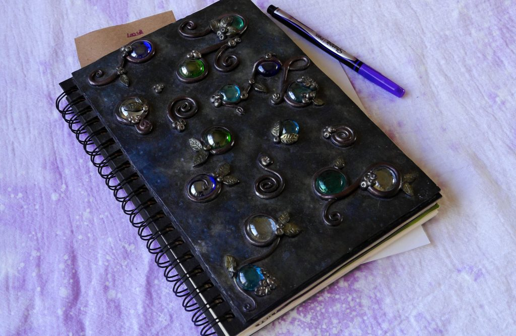Book of shadow, grimoire, spell book, magick book, sketchbook with polymer clay cover on a lavender cloth with sharpie pens.