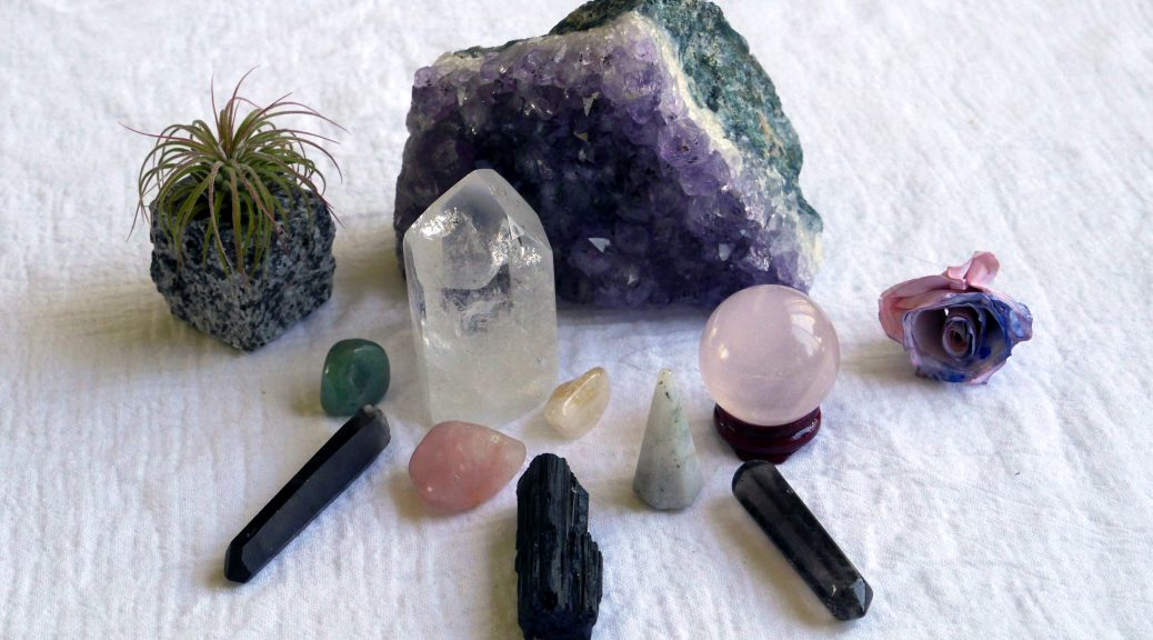 Crystals sitting on a white counter with a small green plant