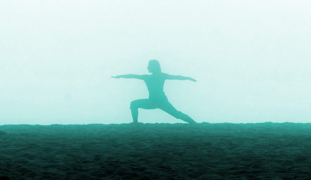 Teal silhouette of a girl doing yoga Warrior Pose on a foggy beach.