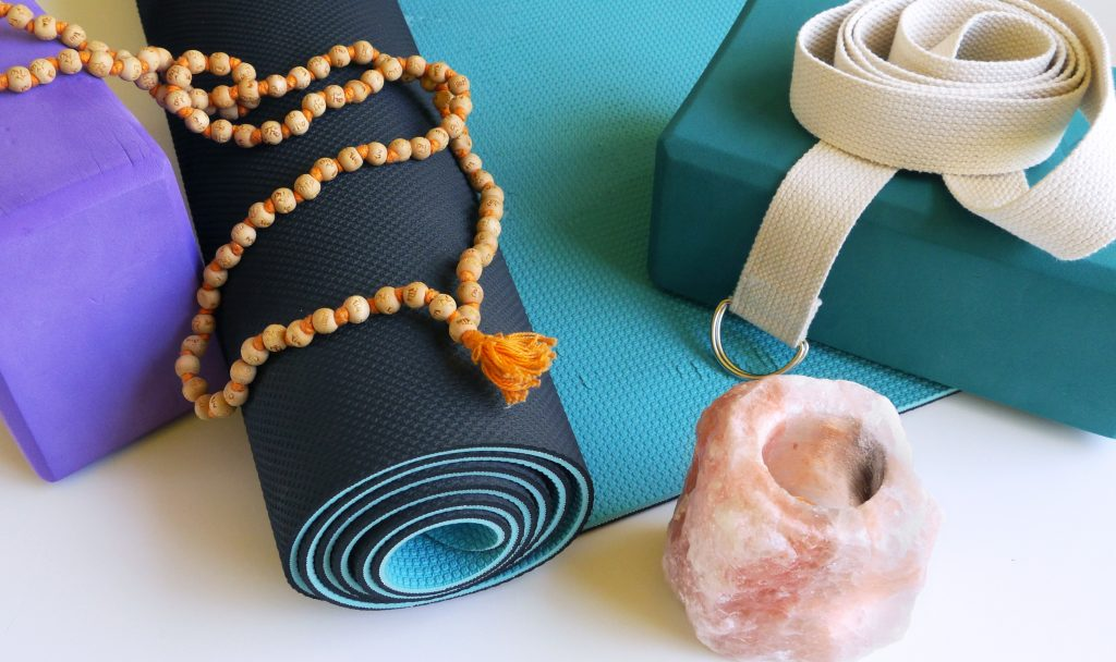 Yoga blocks in teal and purple, ThinkSport non-toxic yoga mat, Japa male beads, yoga strap, and Himalayan rock salt candle.