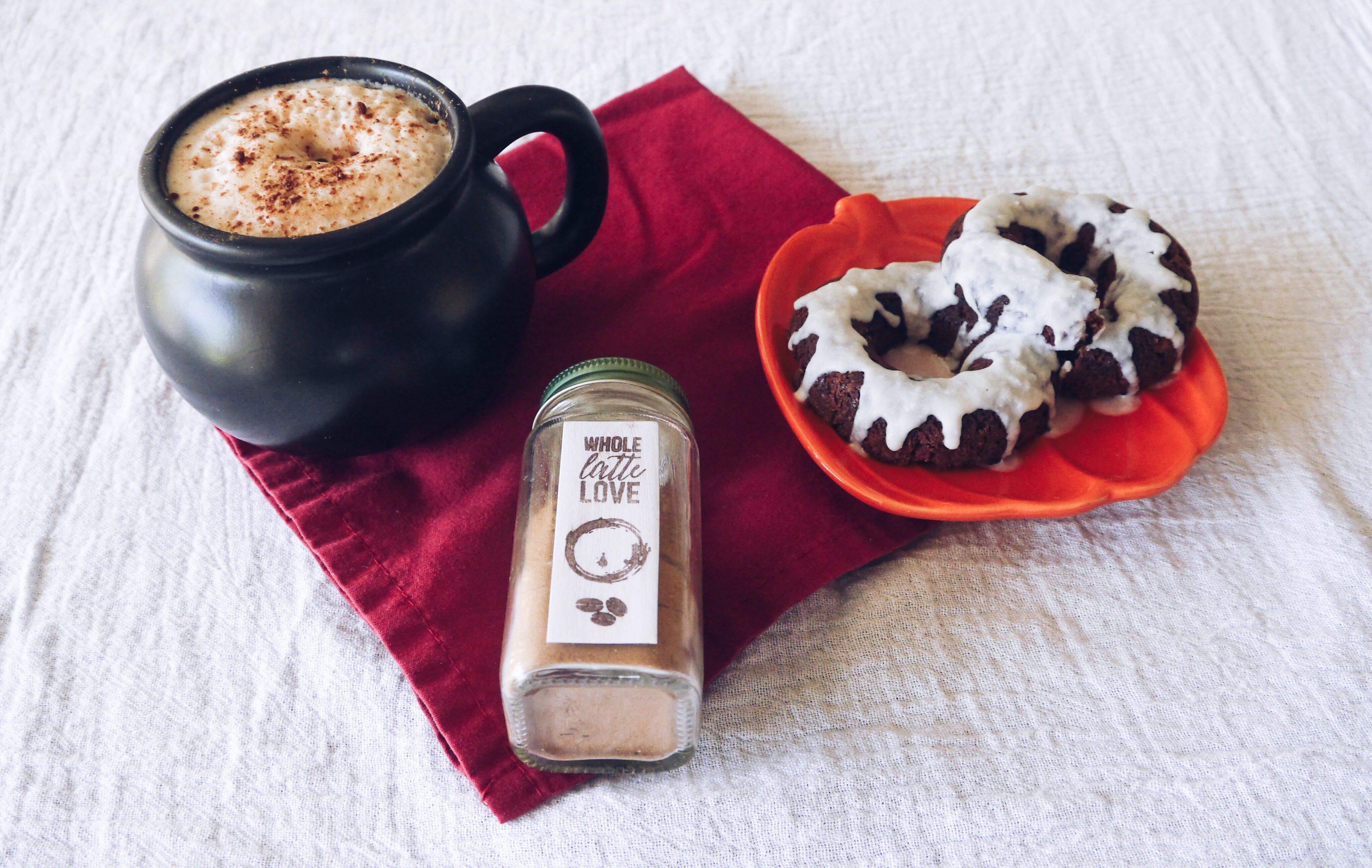 Cauldron mug with latte, coffee spice, and vegan chocolate doughnuts on a pumpkin plate.