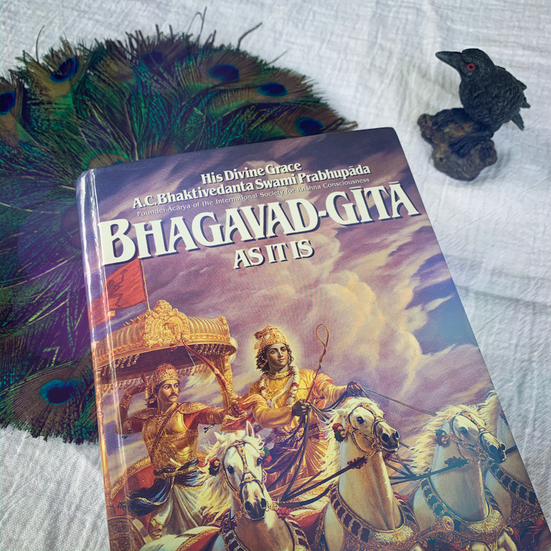 Bhagavad-Gita with a peacock fan and a raven figurine