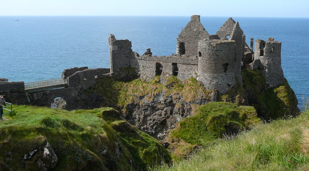 Dunluce Castle ruins on a cliff overlooking the ocean.