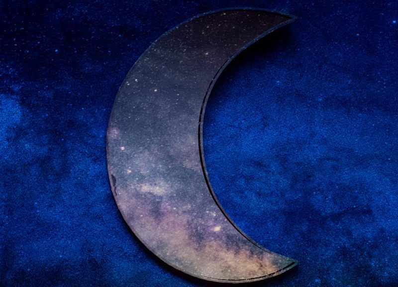 A moon-shaped mirror on a dark blue background reflecting stars and cosmic dust