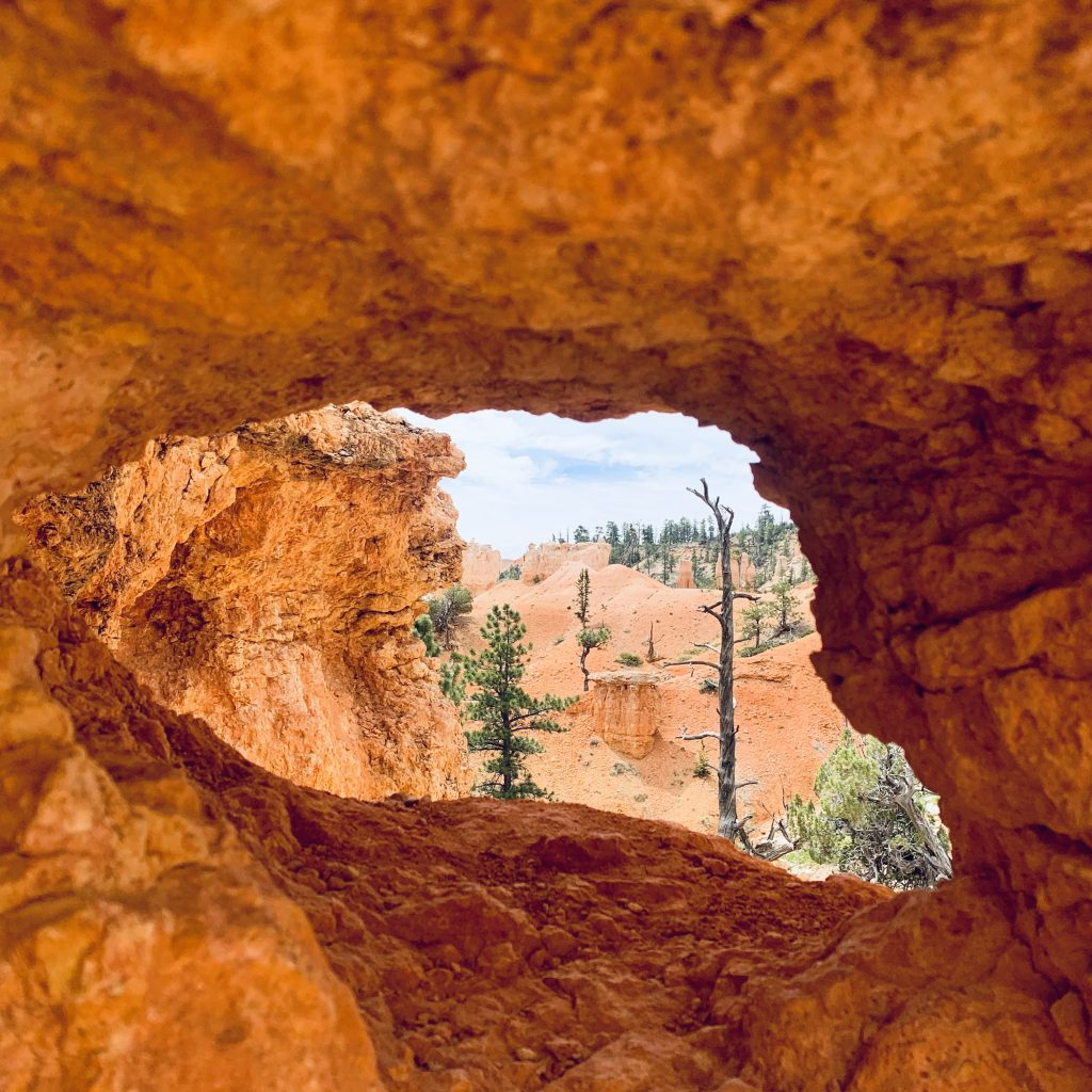 Looking through a large hole in red-orange rocks to a surreal, desert canyon landscape.