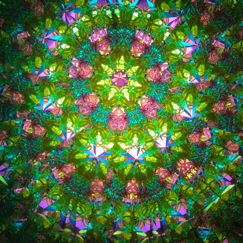 Green and pink interior of a kaleidoscope. Illusion. Glamour